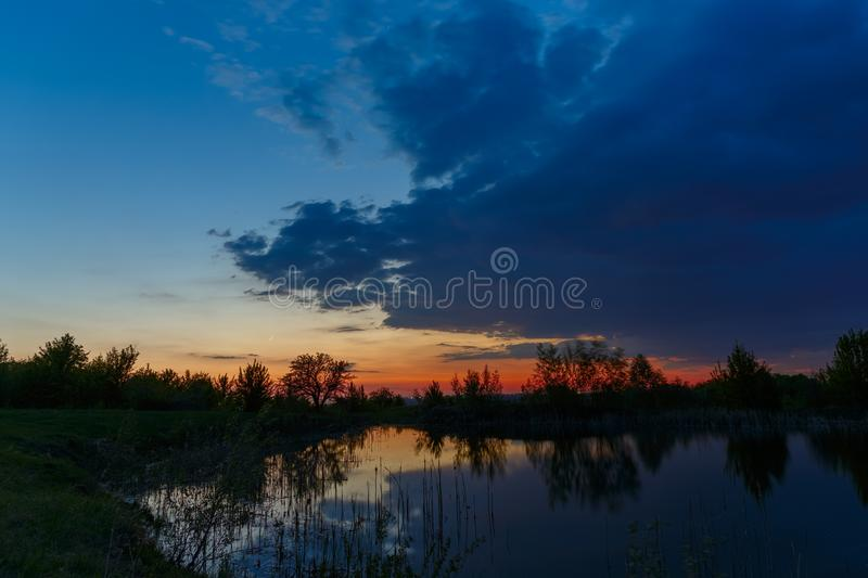 The sky with bright clouds lit by the sun after sunset over the lake.  stock photos
