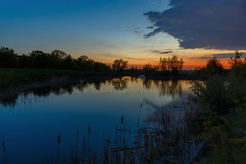 The sky with bright clouds lit by the sun after sunset over the lake.  stock photo