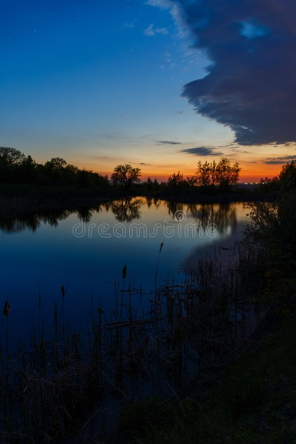 The sky with bright clouds lit by the sun after sunset over the lake.  stock image
