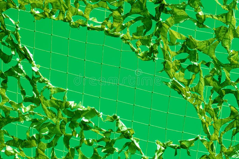 Sky camouflage net military torn light white green ufo yellow shadow. Green military mesh with torn holes with shadows from bright sunlight. Camouflage net and royalty free stock image
