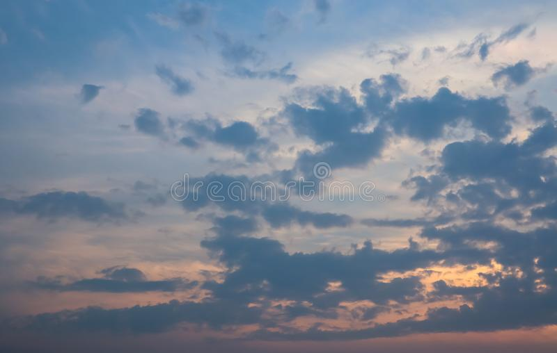 Sky and cloud at the sunset time. The orange warm light frome the sunset spread out the light through the cloud. Background image stock photo