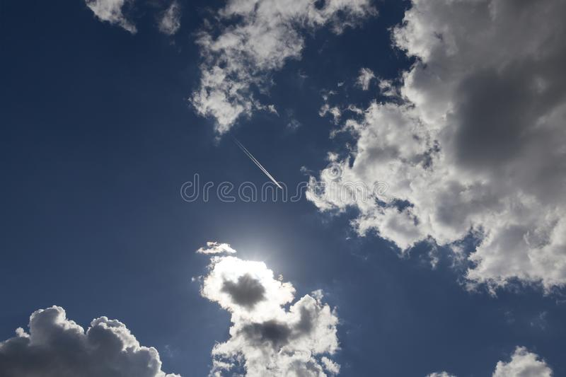 Sky clouds. Flying high in the sky plane, behind which there was a white inversion trail from the engine, against a background of blue sky and white cumulus stock image
