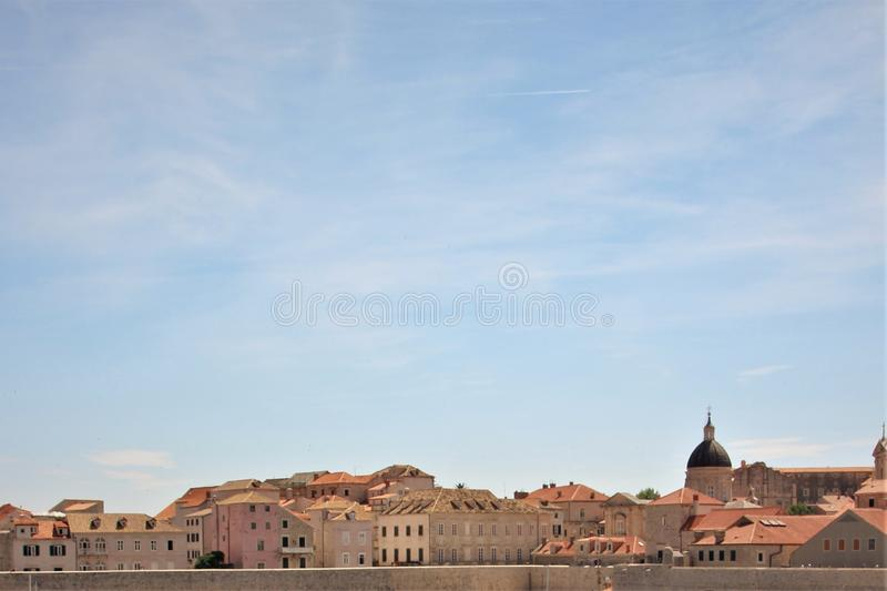 Sky and clouds over the city of Dubrovnik, Croatia, on a sunny day. Beautiful blue sky with light white clouds over the ancient architecture of the famous stock image