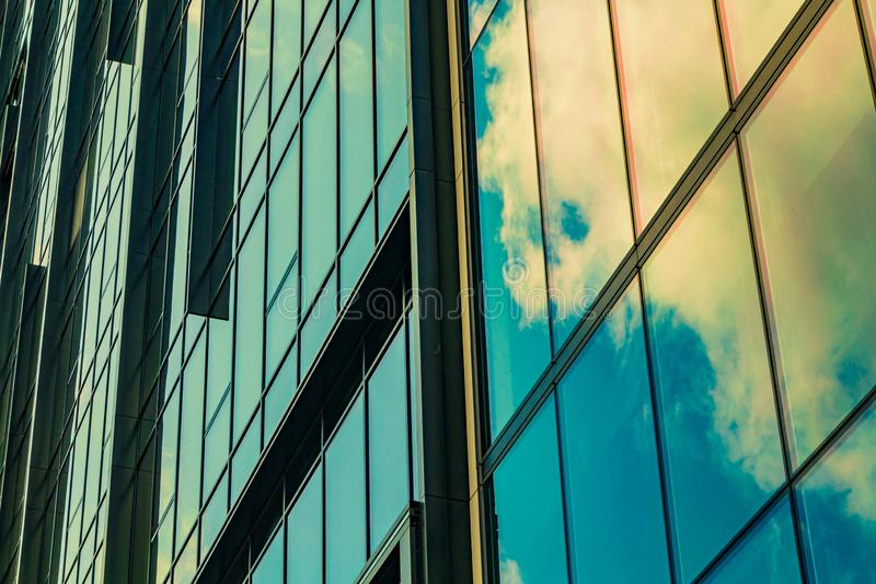 Sky with clouds reflected in windows of modern office building. Colorful background stock photo