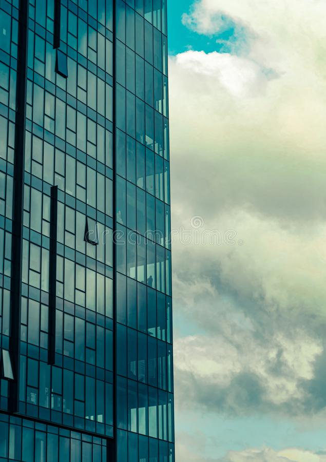 Sky with clouds reflected in windows of modern office building stock photos