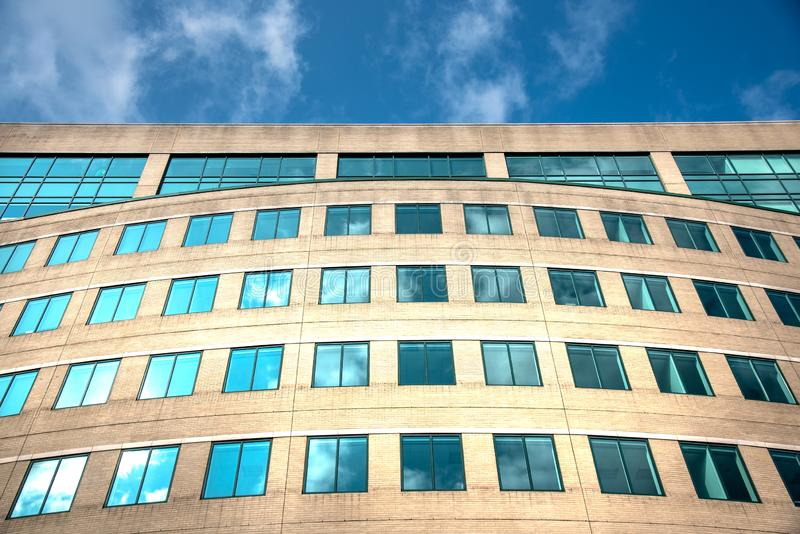 Sky and clouds reflecting on green tinted windows on generic commercial building royalty free stock photo