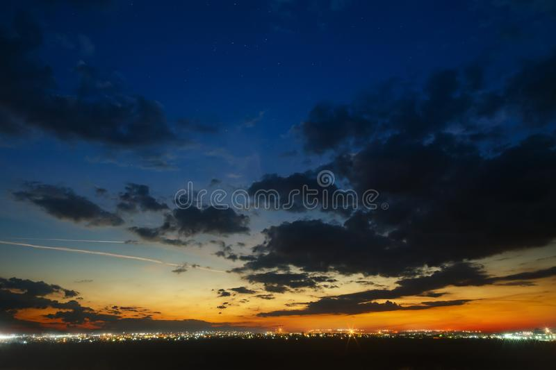 Sky with clouds after sunset over the city with street light.  royalty free stock image
