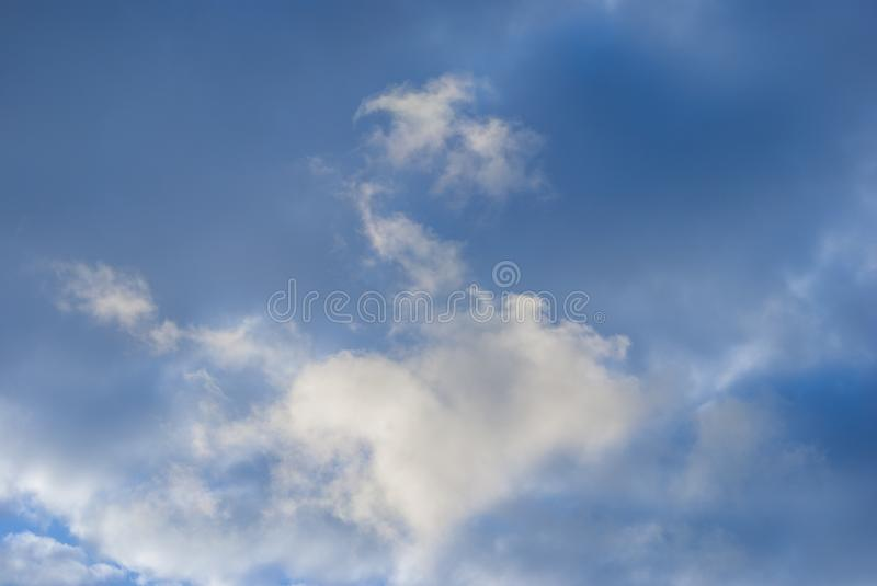 Sky with clouds to form drawings. White clouds in blue sky to form shapes and textures stock photography