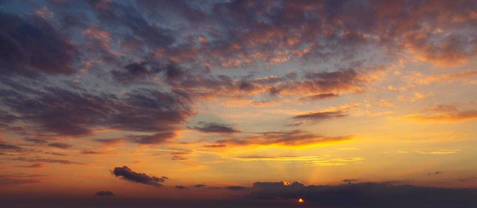 Sky during a colorful, bright orange sunset, sun`s rays make their way through the clouds stock images