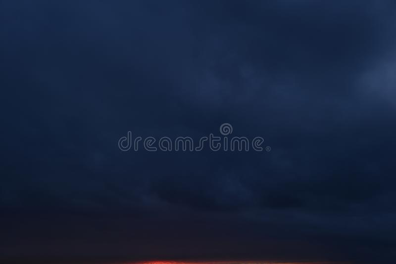 Only sky is a dark blue cloudy bright red stripe of twilight light the atmospheric nature. Nature abstract Only sky is a dark blue cloudy bright red stripe of stock photo