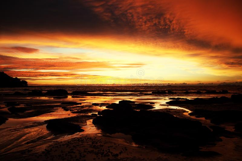 Sky with deep hanging storm clouds and wet sludge during low tide swathed in yellow and red bright light during sunset royalty free stock image