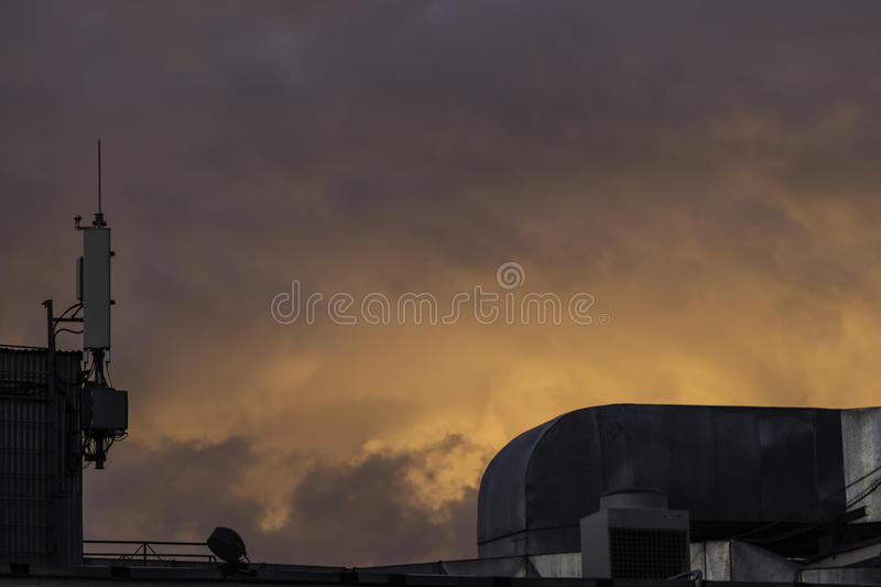 Sky on fire. A gritty urban rooftop and thunderclouds at sunset create an apocalyptic feel stock photography