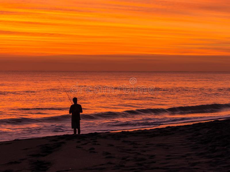 Sky on Fire over a Florida Beach. Landscape background of the sky lighting up bright orange before dawn over a Florida beach as a surf fishermen stands on the royalty free stock photo