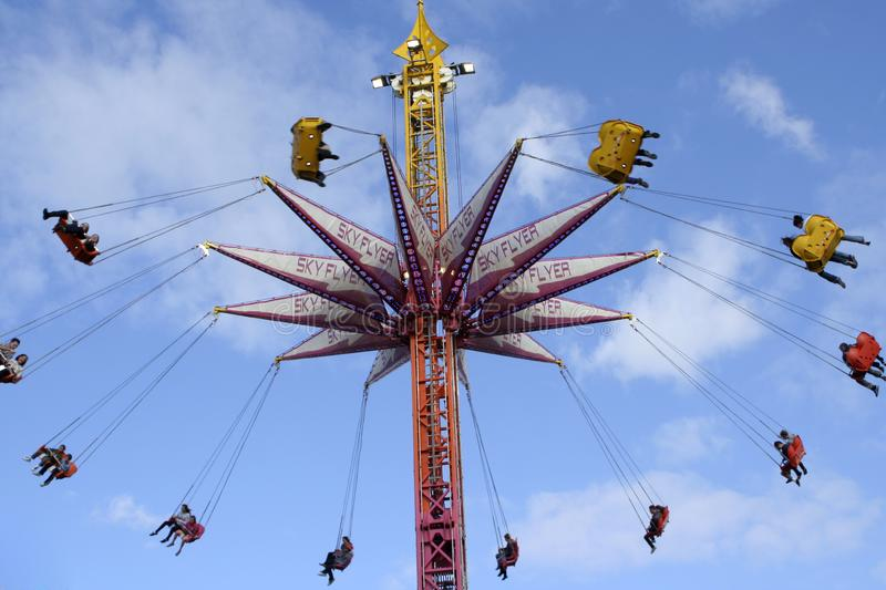 Sky High Ride. Sky-high entertainment ride at a show with people in coloured seats swinging in circular fashion against a blue ky with white clouds stock photo