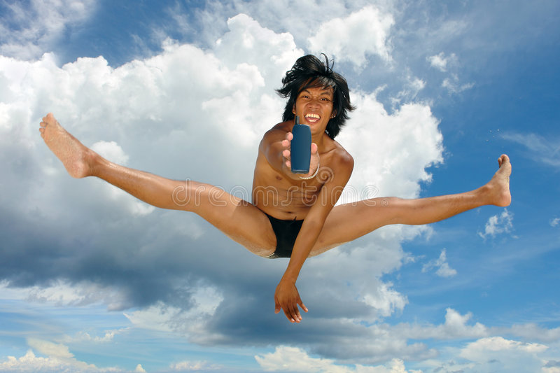 Sky jump with cellphone. Cheering enthusiast Asian teenager in swimsuit jumping high in the air, sky with cloudscape, showing blank cellphone with copy space