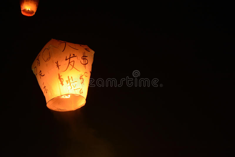 Sky lantern floating into the night sky at the festival in Pingxi, the Chinese text is a wish for money in the New Year stock image