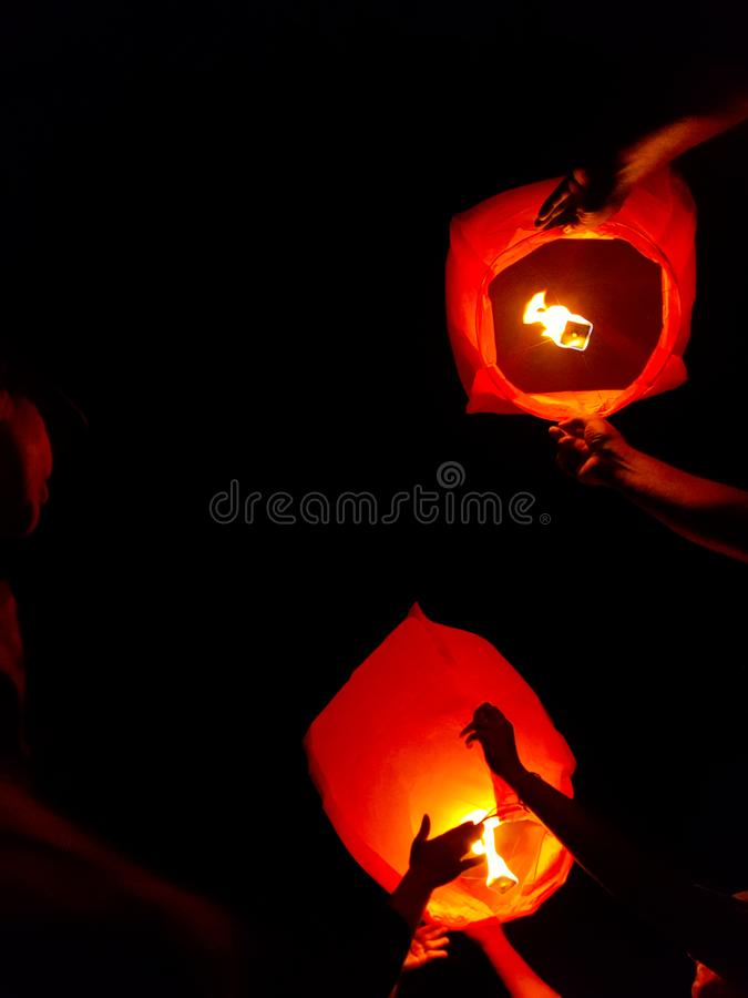 An indian woman releasing a lighted paper hot air balloon in sky lantern festival.  stock photography