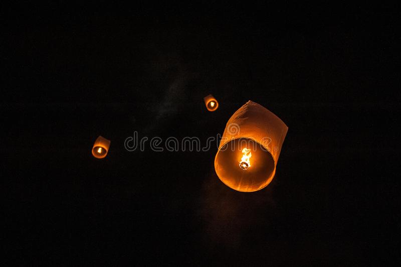 Sky lanterns, flying lanterns, floating lanterns, hot-air balloons on dark night sky with moon. New year and Yeepeng festival royalty free stock photography