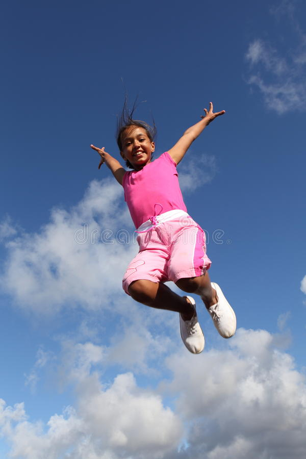 Sky is the limit jump for joy by young school girl stock photos