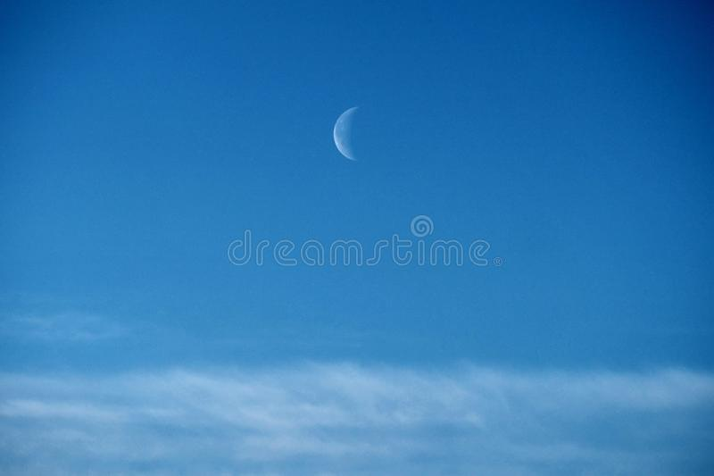 Moon and clouds observing on blue ksy royalty free stock image