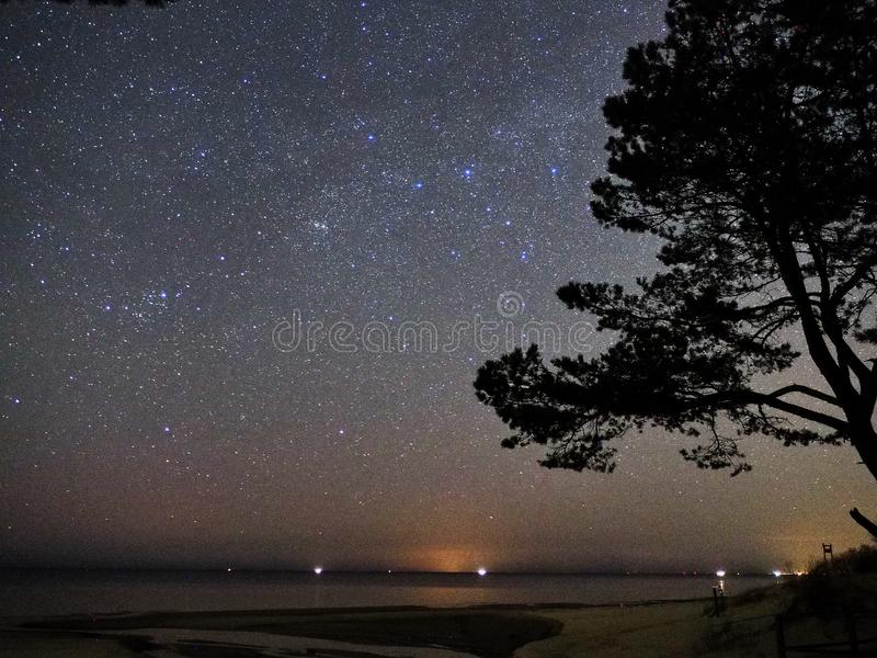 Night sky and milky way stars, Perseus and Cassiopeia constellation over sea royalty free stock photos