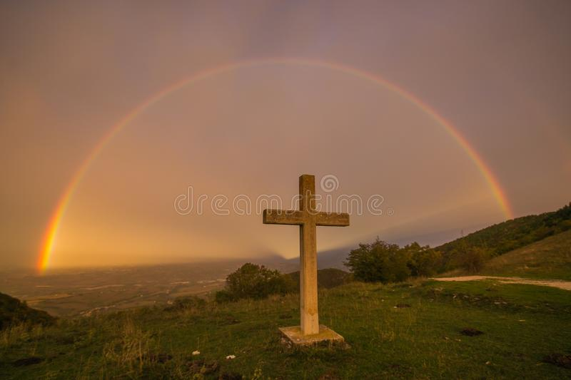 The sky of paradise with wonderful rainbow and cross. Marche, Italy royalty free stock photo