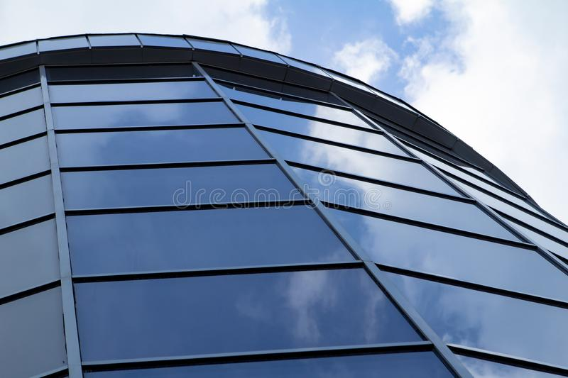 Sky reflected in a modern building blue glass facade stock image