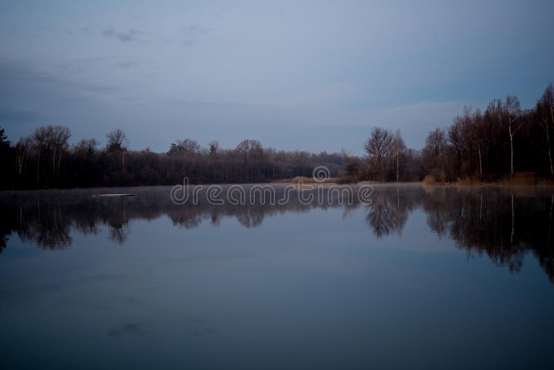 The sky reflects on the water of a lake at daybreak stock photography