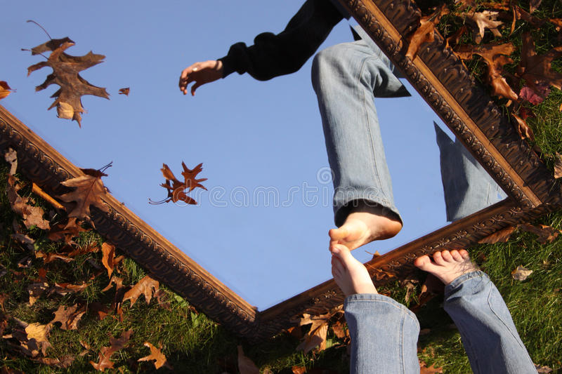 The Sky's the Limit. A surreal image of a person stepping into a mirror, flipped 180 degrees royalty free stock image