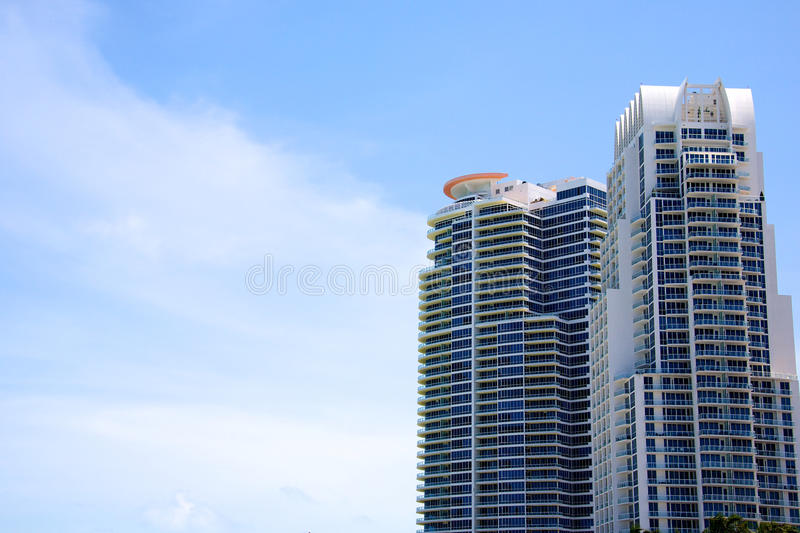 Sky scrapers. Two large modern sky scrapers against a lightly clouded sky royalty free stock photography
