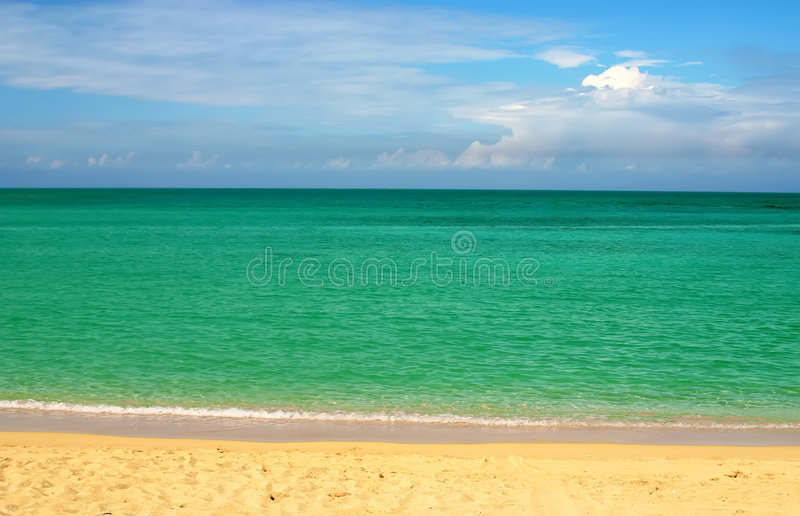Sky, sea & clouds. Simple composition: ocean over blue sky and sand royalty free stock photography