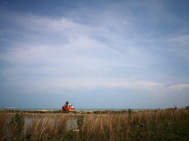 Lonely small ship. Small ship. Boat. sea. blue. long grass. Beach royalty free stock image