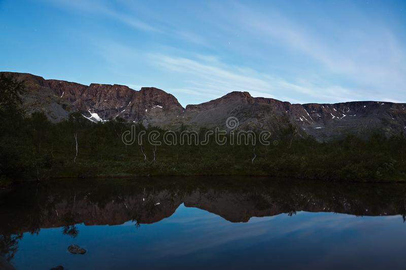 The sky with the stars at dawn, reflected in the water. Of a mountain lake stock photo
