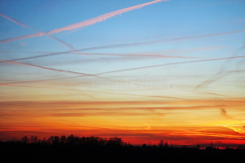 sky at sunset, the clouds are colored red by the sun that in a while will make room for the moon stock photography