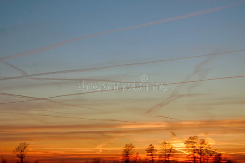 sky at sunset, the clouds are colored red by the sun that in a while will make room for the moon stock images