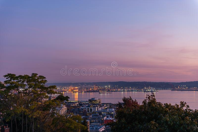 The sky takes on a purple tone at dusk in the port of Seattle and Elliott Bay. The sky takes on a purple tone at dusk in the port of Seattle and Elliott Bay stock photos