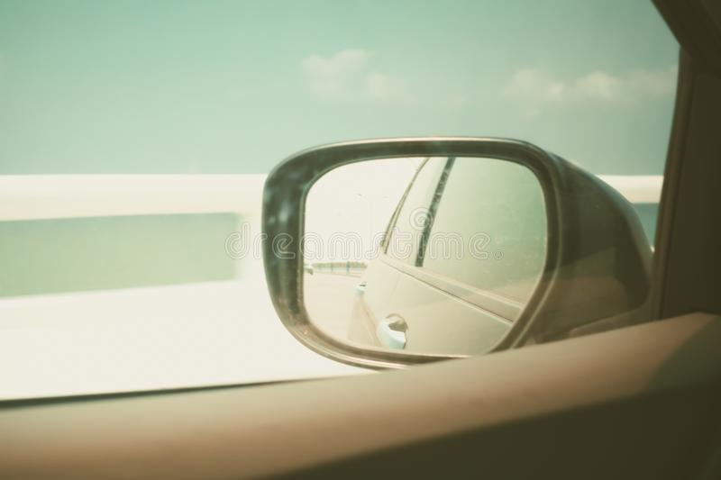 Sky view from car window and side view of black car in wing mirror while driving stock photography