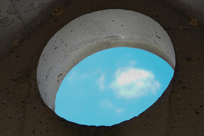 Sky view through a round hole of the old stone wall of a house stock photography