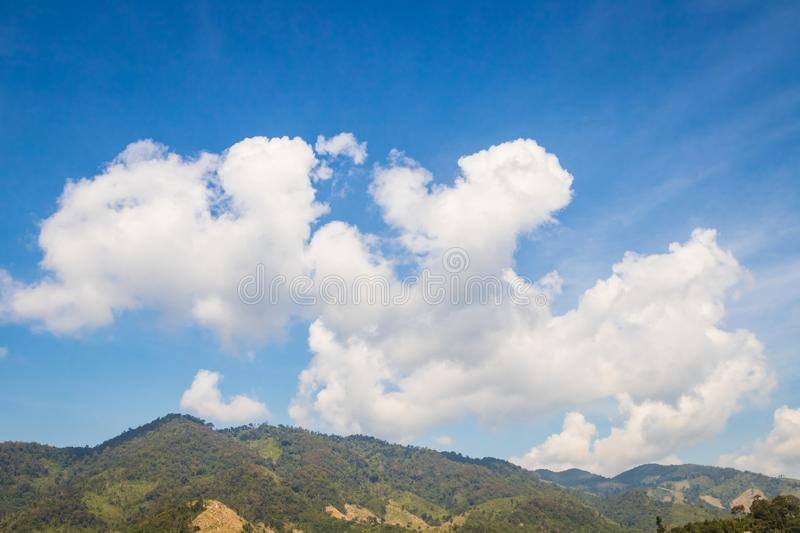 Sky with white clouds floating over mountains stock photos