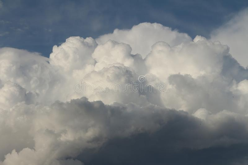Huge cottony clouds called cumulus nimbus with the blue sky behind. stock photos
