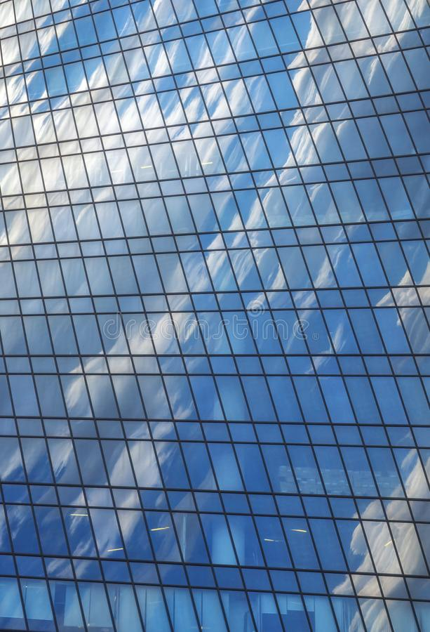Sky and white clouds are reflected in glass wall of modern skyscraper. The sky and white clouds are reflected in the glass wall of the skyscraper building royalty free stock images
