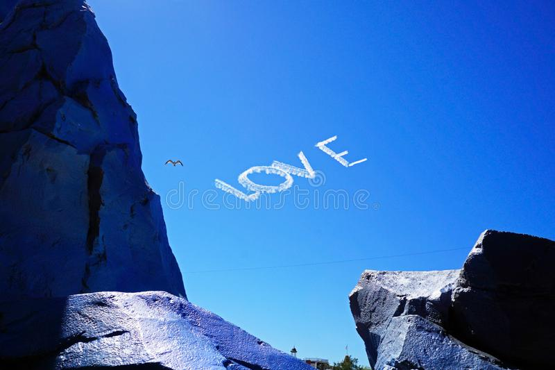A sky writer writing the word Love in the sky stock photos