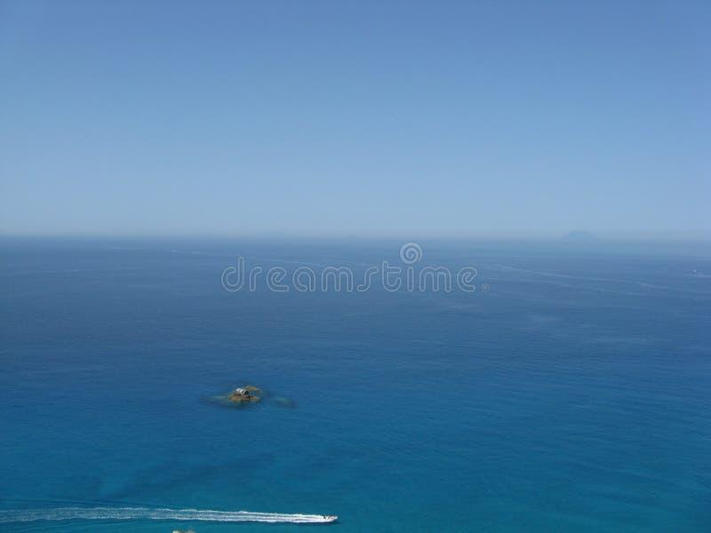 Skyblue hav med den steniga ön och Stromboli arkivfoton