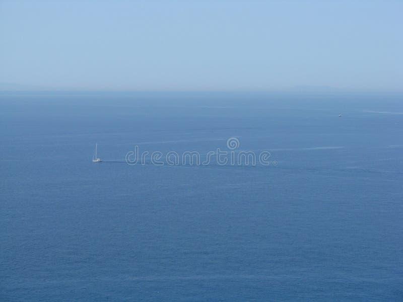 Skyblue hav med fartyg och Stromboli arkivfoto
