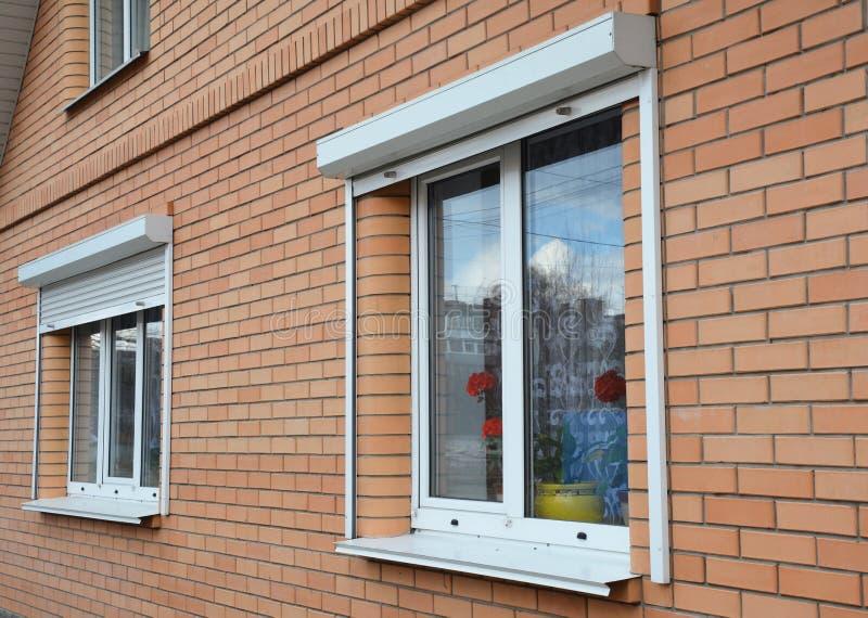 Skydd för fönster för hus för rullningsslutare Tegelstenhus med metallrullslutare på fönstren royaltyfri fotografi