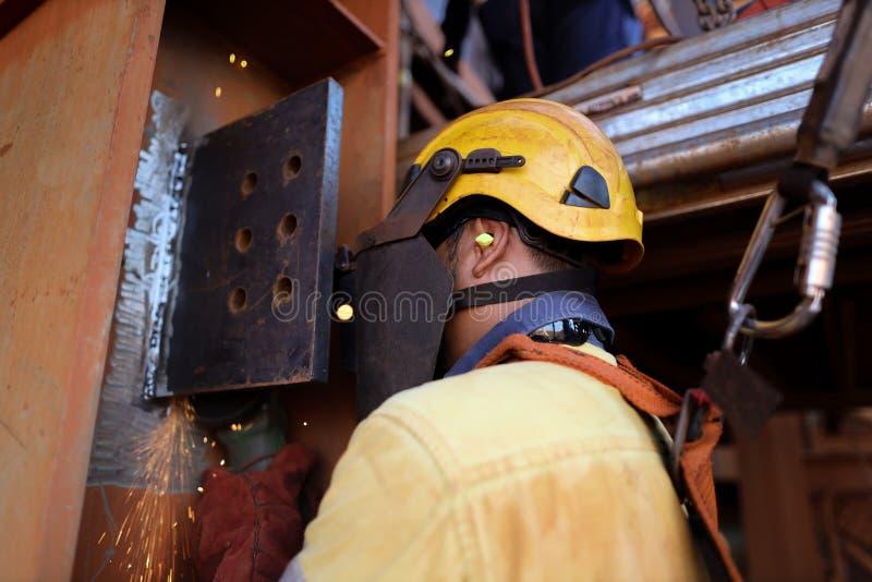 Skydd för nedgång för sele för säkerhet för hjälm för reptillträdeswelder bärande genom att använda skydd för öraproppoväsen, med arkivbild