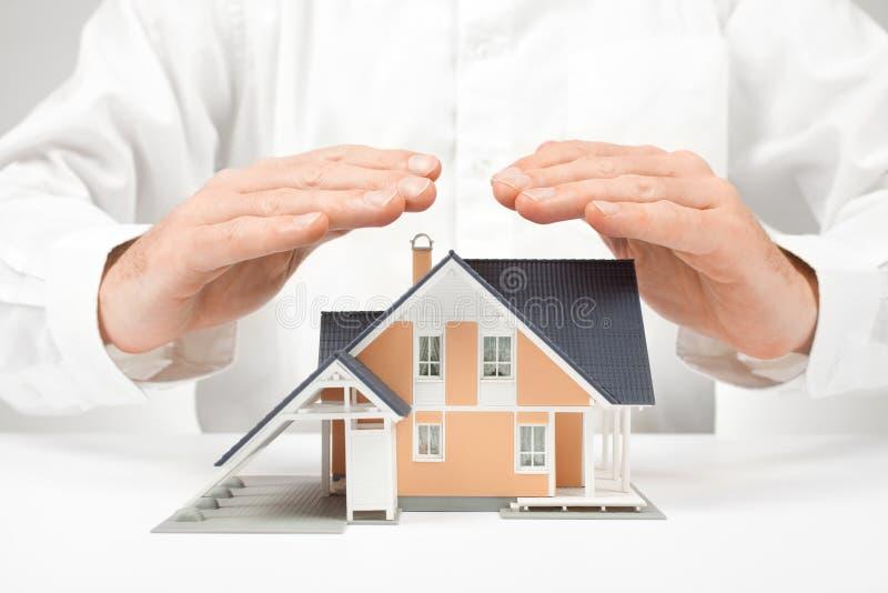 Skydda huset - försäkringbegrepp royaltyfria bilder