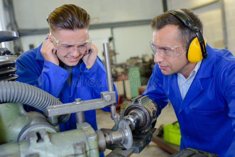 Skyddande öron för ung man från bullrigt maskineri arkivbild