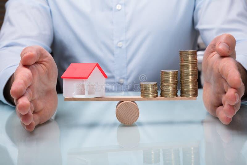 Skyddande jämvikt mellan husmodellen And Stacked Coins arkivbild