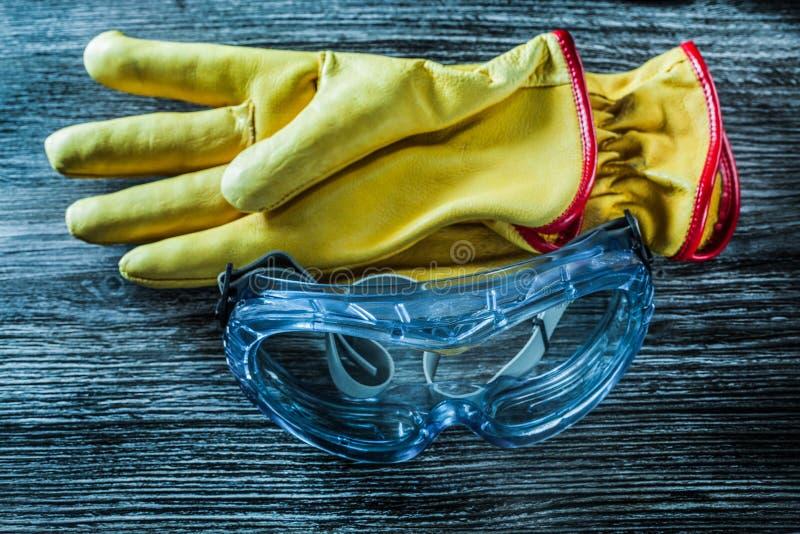 Skyddande piska handskeexponeringsglas på träbräde fotografering för bildbyråer